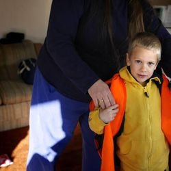 Noah Talbot gets into the reflective vest that he wears to and from school with the help of his mother at his South Jordan home  on December 15, 2010.