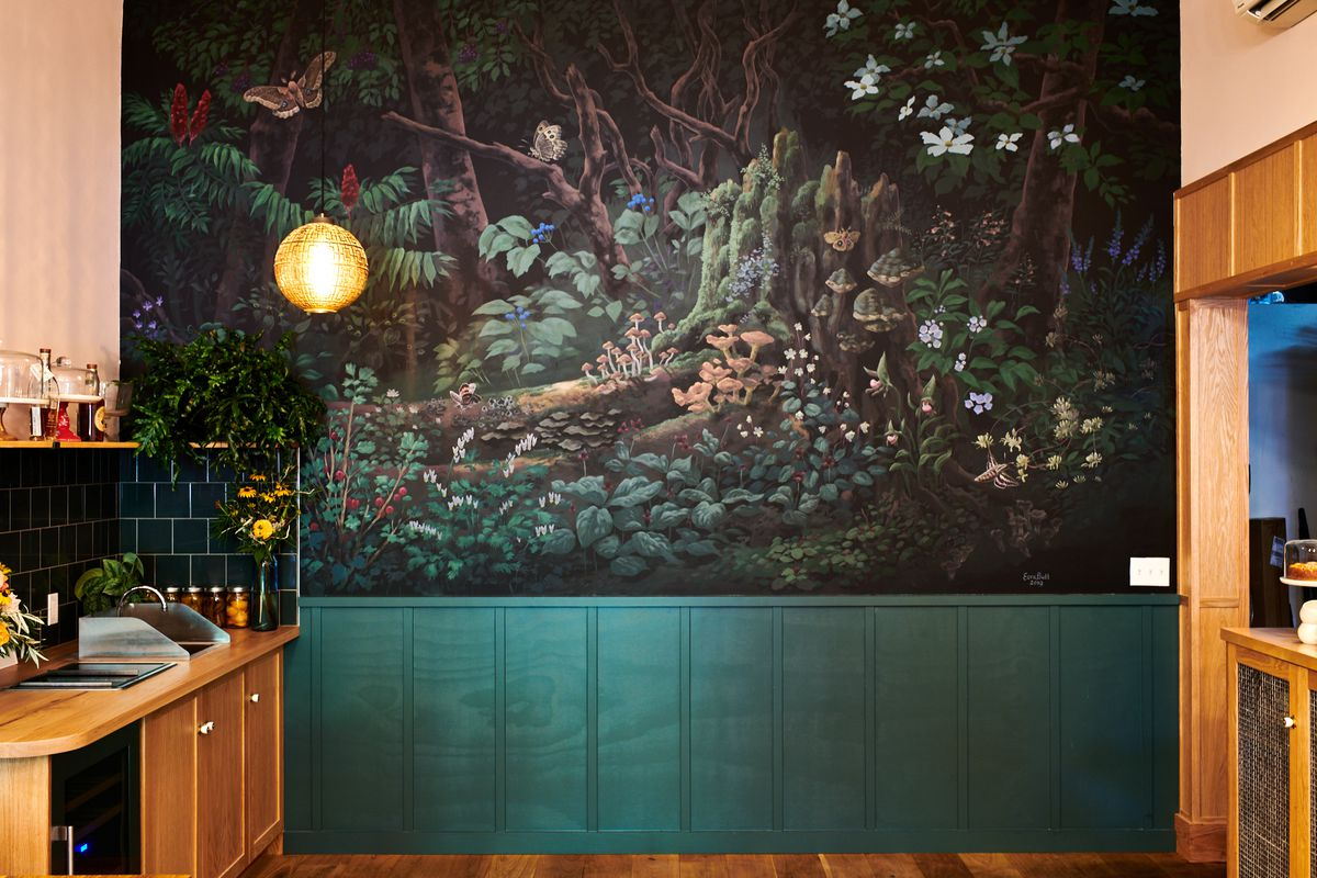 The scene, featuring mushrooms, leaves, and small flowers in a wooded area, is meant to represent Lovelace's hometown and the botanicals native to North Carolina