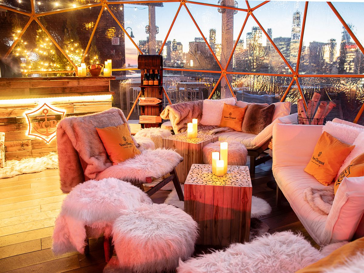 White couches and chairs with white fur throws and the city skyline behind