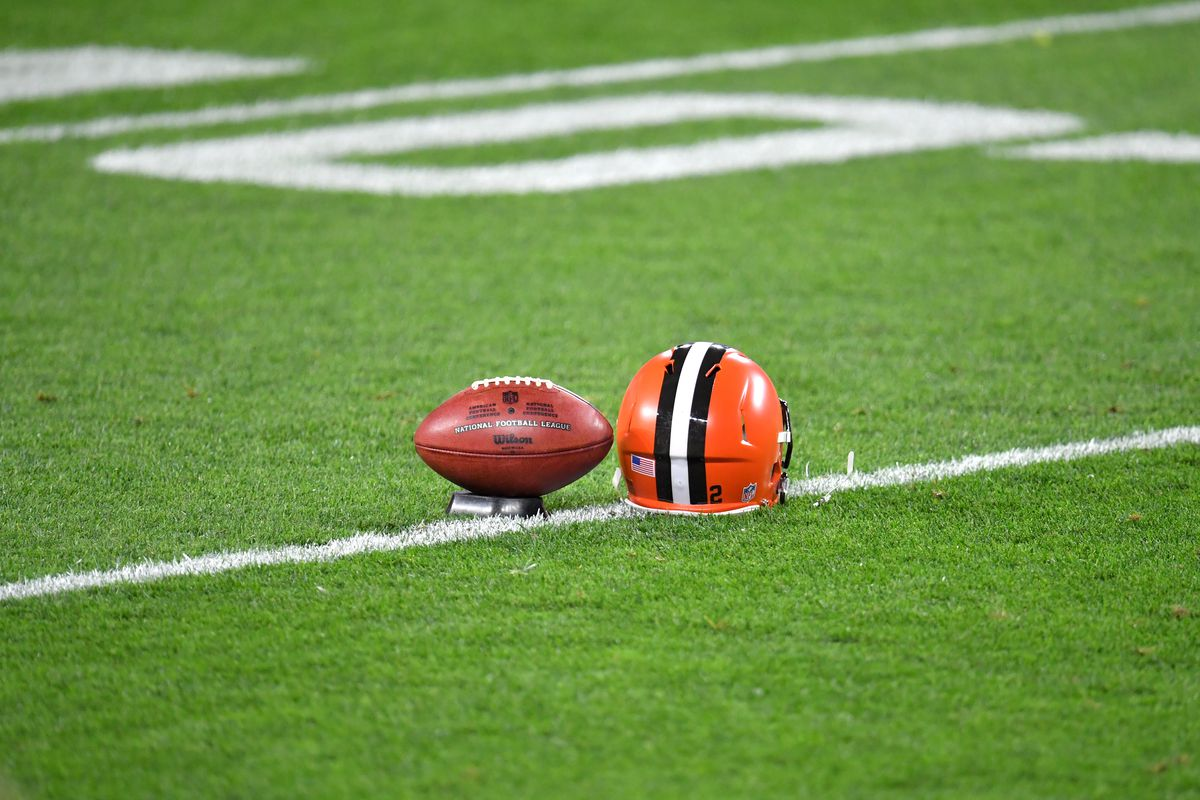An official NFL football sits next to a Cleveland Browns helmet on the field prior to the prior to the game between the Cleveland Browns and the Cincinnati Bengals at FirstEnergy Stadium on September 17, 2020 in Cleveland, Ohio.