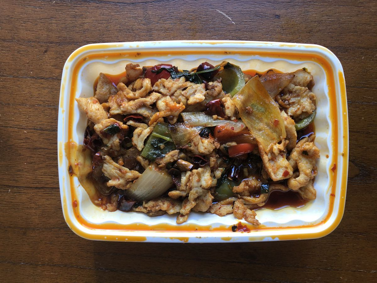 A plastic tray of food containing thin slices of chicken, chilies, peppers, and onions called cumin chicken