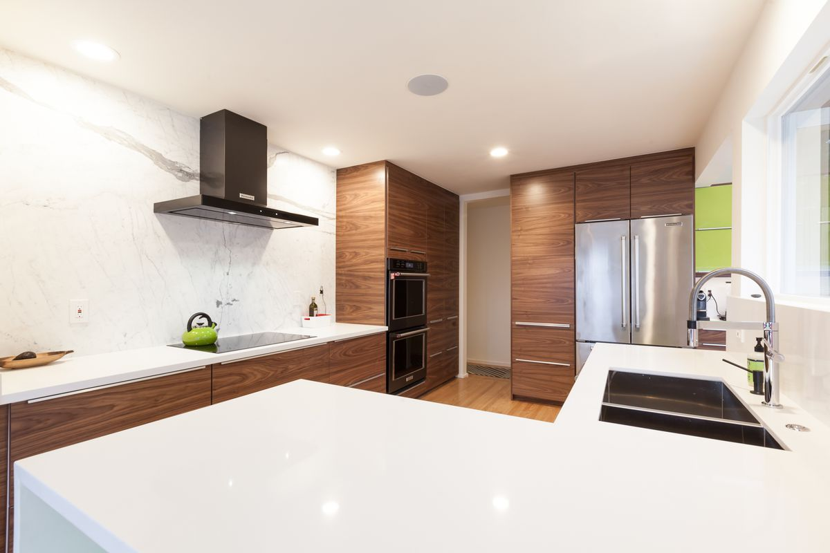 A kitchen area with white countertops, wood cabinetry, and windows.