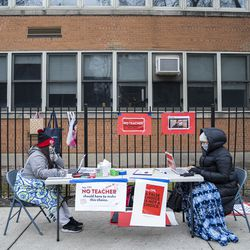 Teachers Adrienne Thomas, left, and Irene Barrera, right set up their computers and materials for their virtual classes outside of Suder elementary in solidarity with pre-K educators forced back into the building at 2022 W Washington Blvd in West Town, Monday, Jan. 11, 2021.