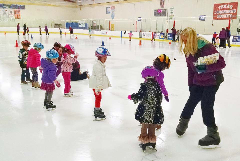 Children and an adult teacher on ice in an ice rink. All of the children are wearing ice skates.