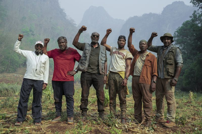 Six men stand with upraised fists.