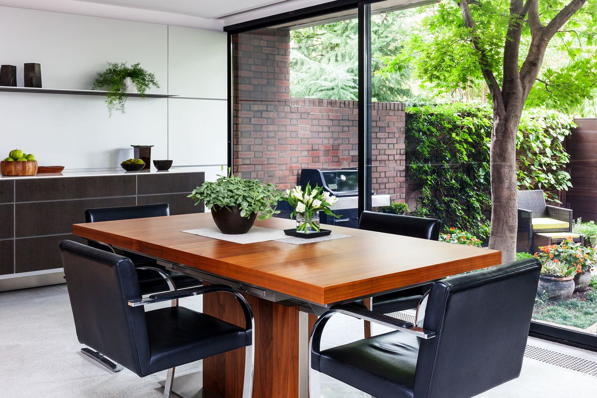 Black leather and metal chairs surround a wooden table.
