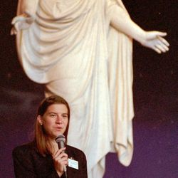 Sister Lana Robison, full-time missionary from Michigan, pauses in front of the Christus in the North Visitors' Center to talk to tour group she is leading around Temple Square in September 2002.