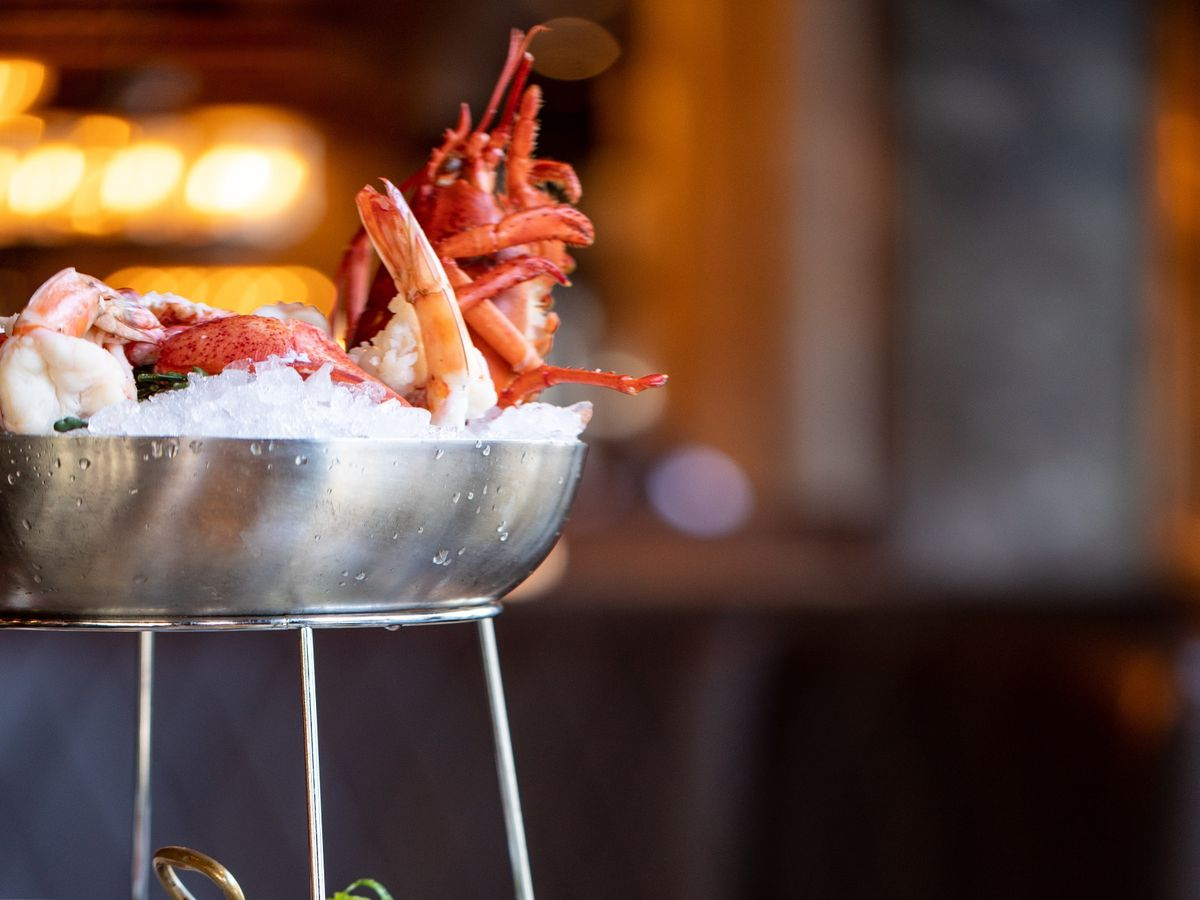 Three-tiered seafood tower with shrimp, clams, oysters, and more