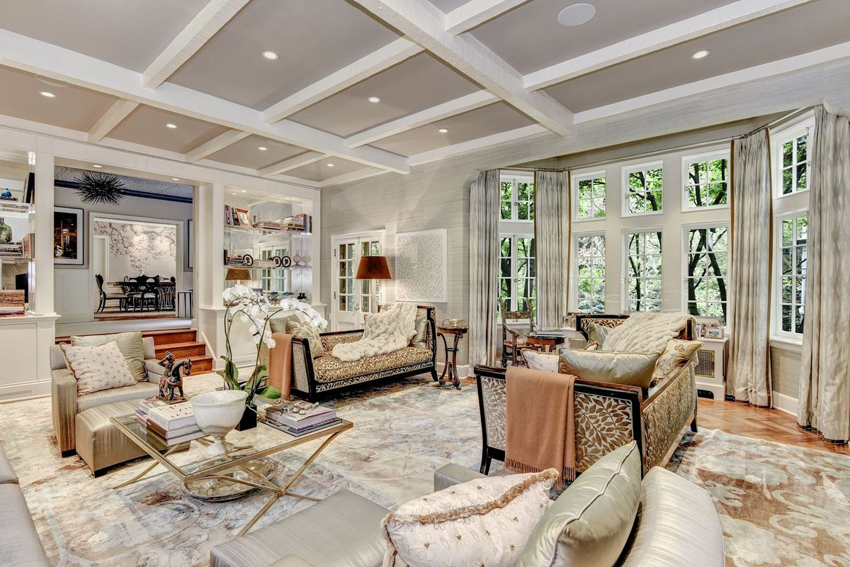 A white and cream formal living room has plentiful seating, white coffered beam ceilings, and large windows.