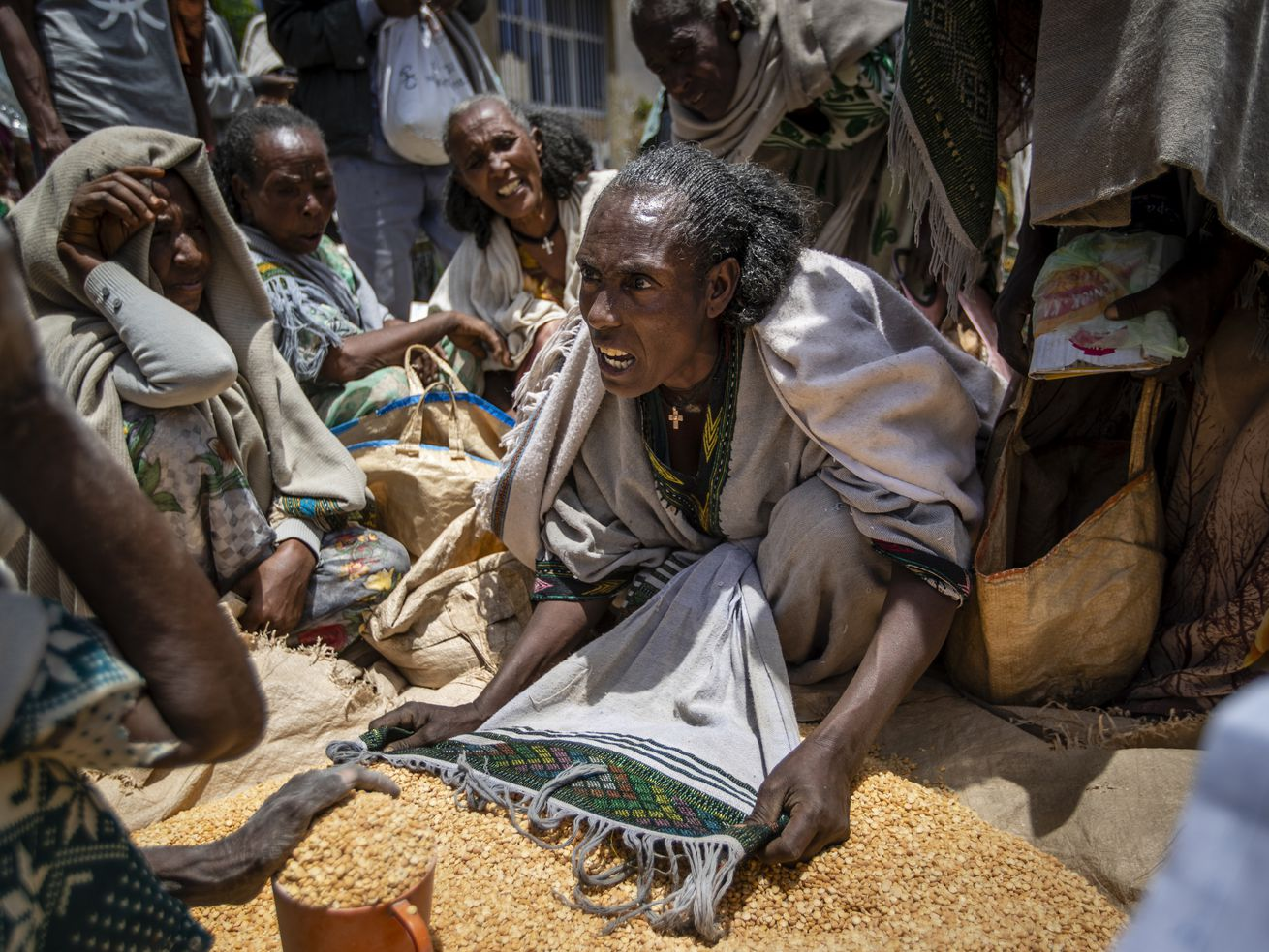 An Ethiopian woman argues with others over the allocation of yellow split peas after it was distributed by the Relief Society of Tigray in the town of Agula, in the Tigray region of northern Ethiopia, on Saturday, May 8, 2021.