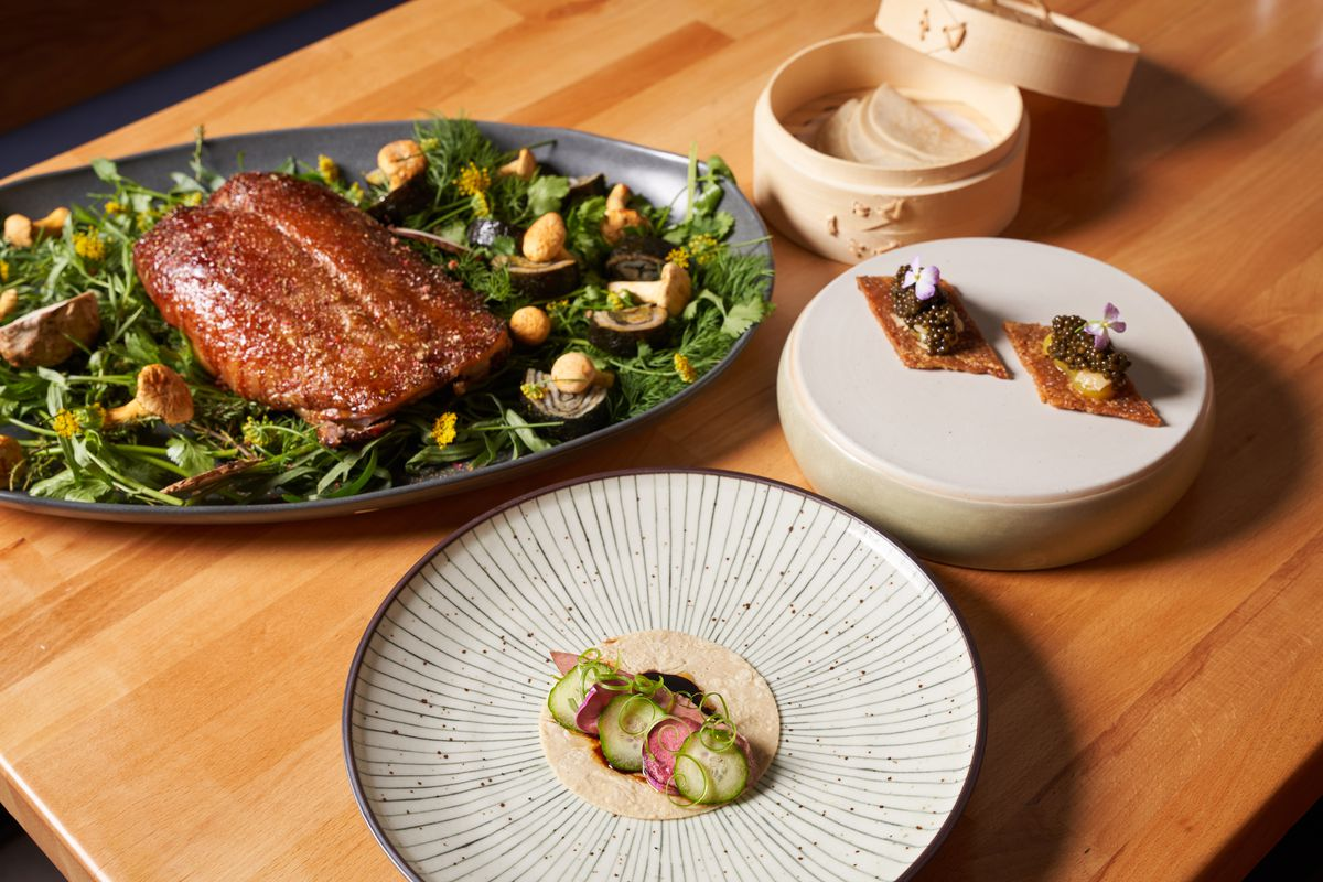 Four dishes with duck, vegetables, and pancakes laid on a wooden table
