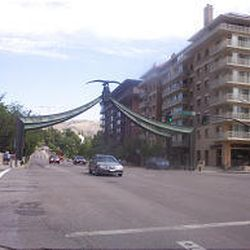The Eagle Gate now spans five lanes of traffic on State Street at South Temple. Brigham Young's Beehive House is visible at the far left.