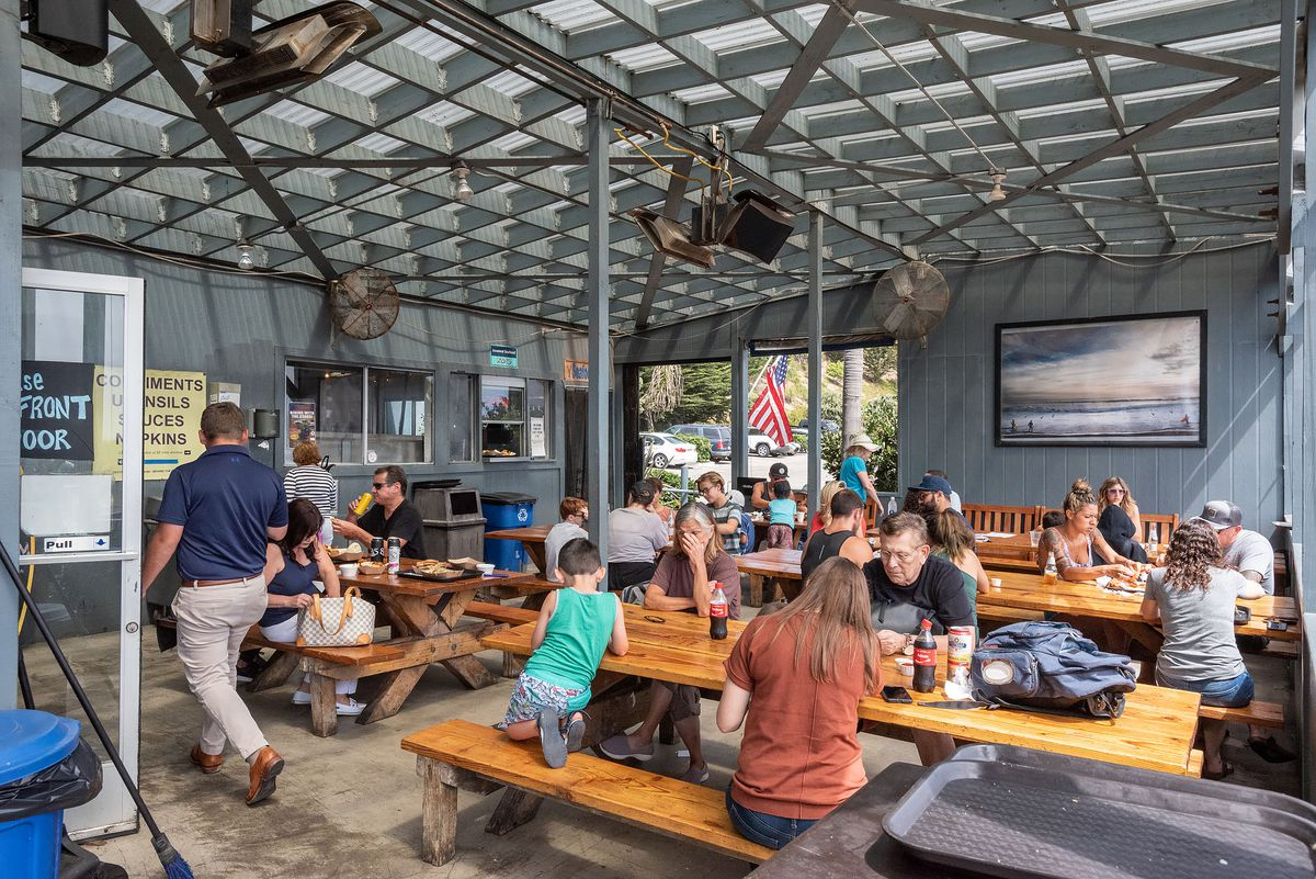 A shaded patio with picnic tables and diners eating seafood.