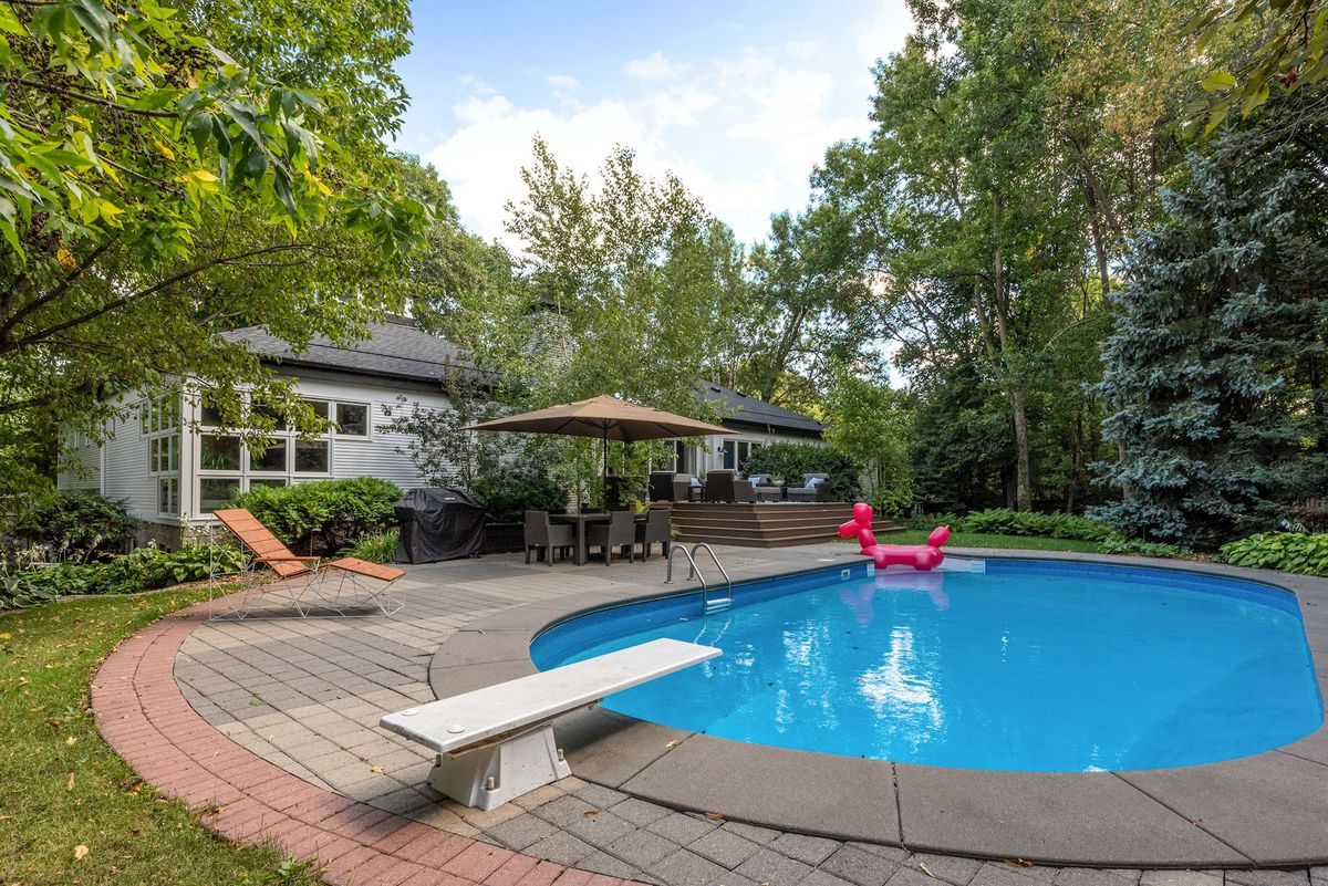 A pool with diving board sits next to a lawn chair and umbrella with table.