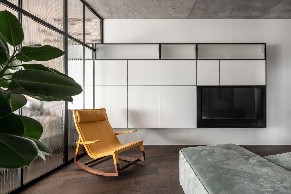 Yellow rocking chair in living room with white cabinets, an interior glass wall, and gray furniture.