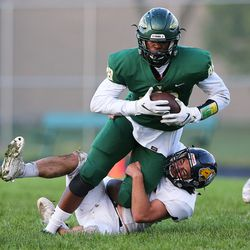 Waubonsie Valley's Damari Wilson (88) makes a reception and holds onto the ball as Neuqua Valley tackler pulls him down.