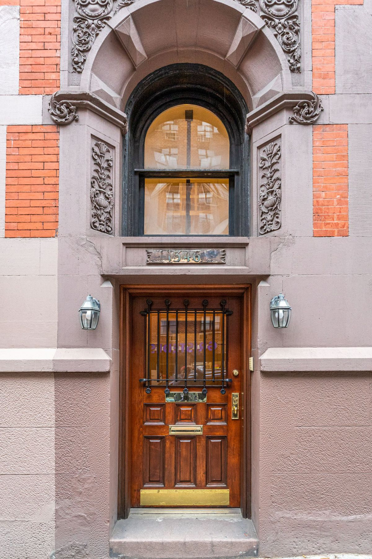 An entrance with terra cotta details, an arched window, and a wooden door.