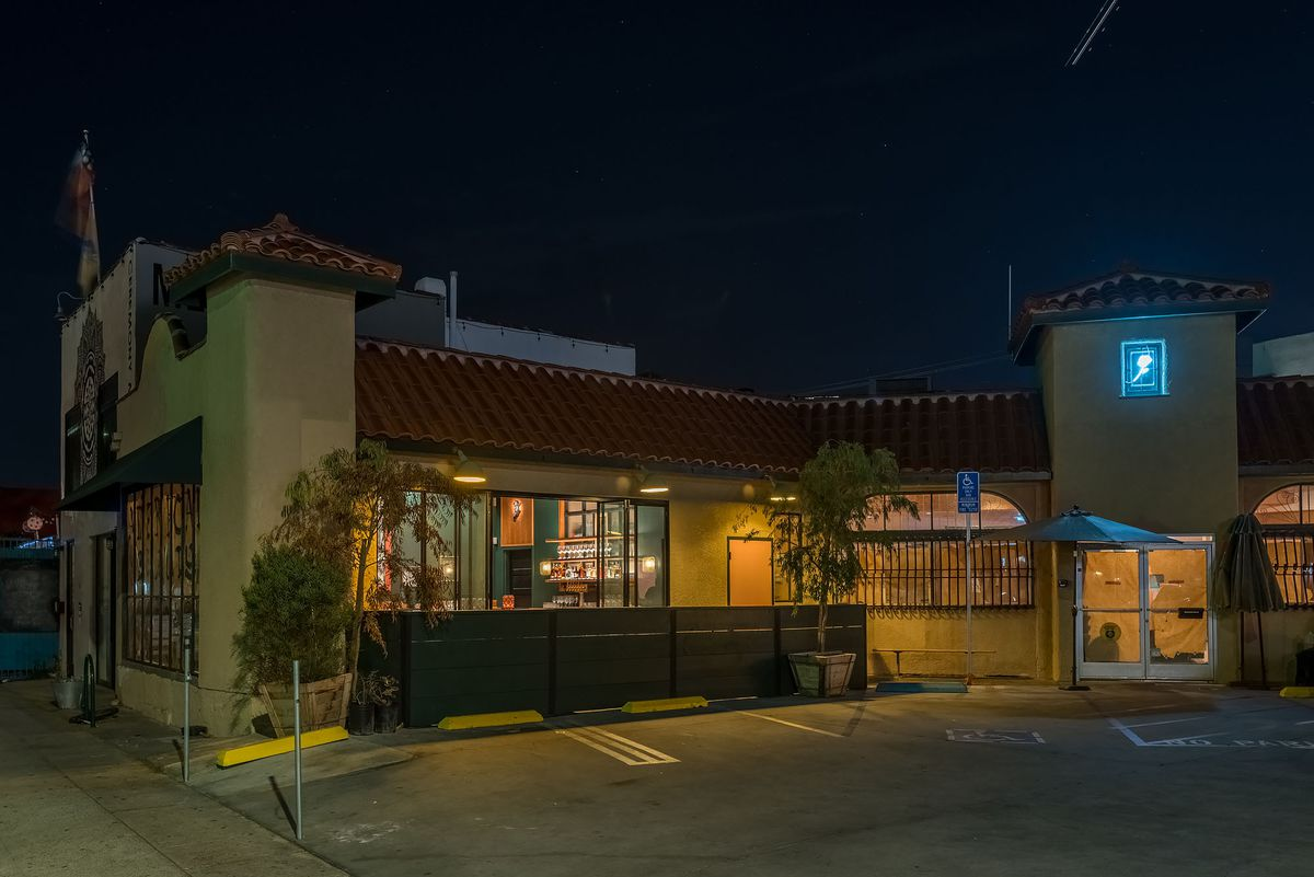 Yellow light splashes on a steakhouse facade in Venice, California.