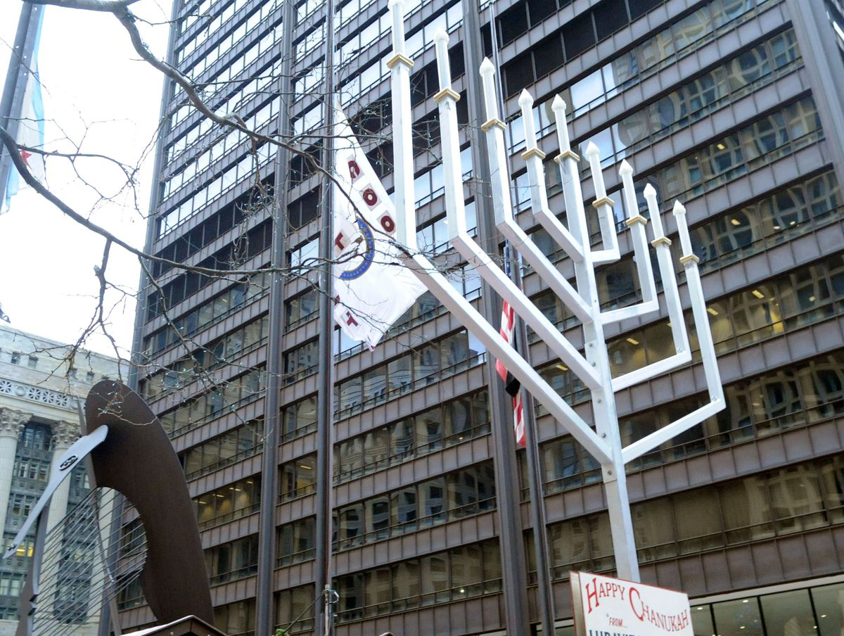 A large menorah on display in a city plaza.