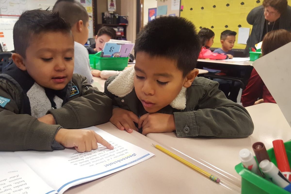 Two first grade boys look at a reading workbook at a desk in a classroom.