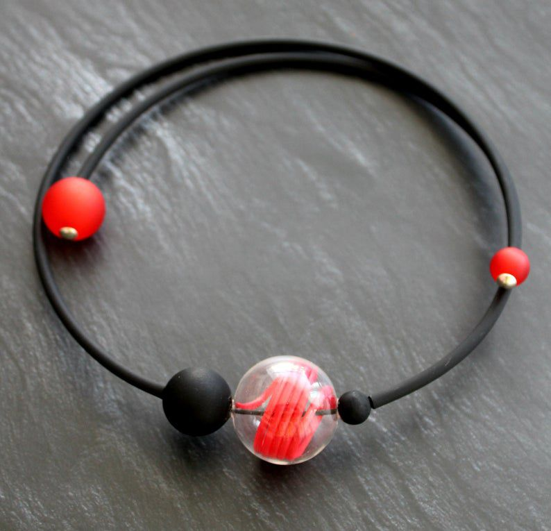Black and red necklace with one black bead and one clear red bead in the center.