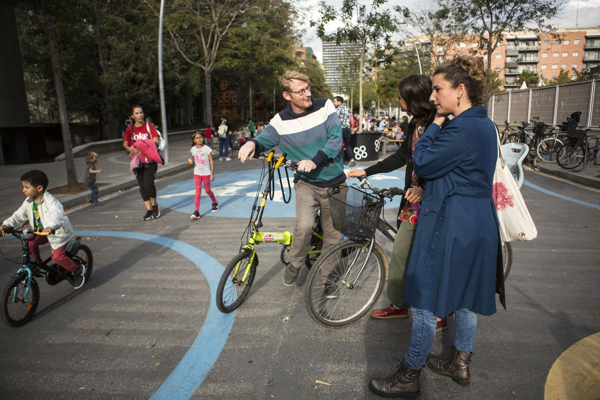 Patrick, Nora, and Silvia, residents of Poblenou, chat in the superblock as kids walk home from school.