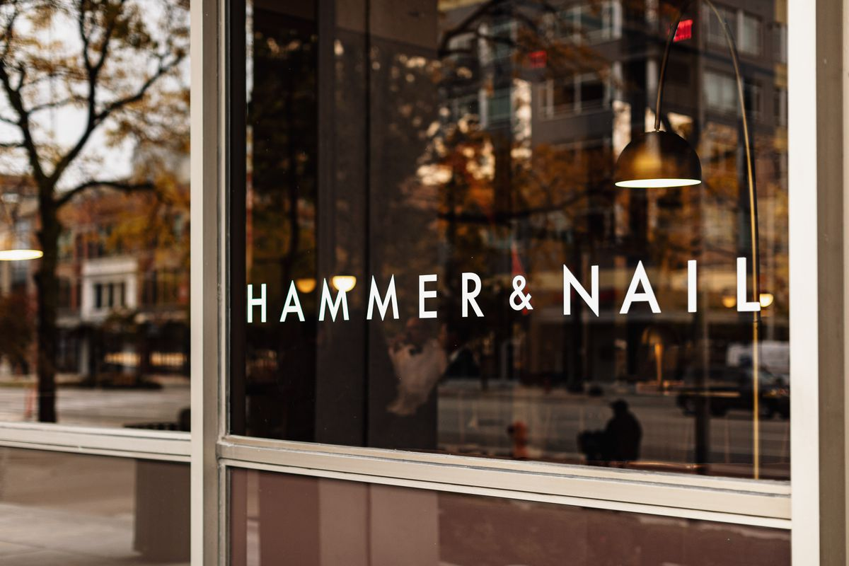 A white window decal spells out Hammer & Nail. Behind the tinted glass men including a bartender in a white jacket with a black bowtie stand around a counter.