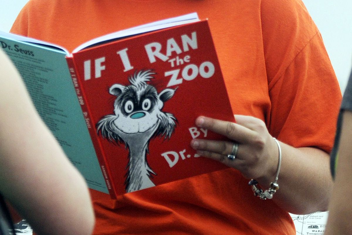 """In this 2013, file photo, Courtney Keating, education coordinator of The Literacy Center in Evansville, Ind., reads """"If I Ran the Zoo,"""" By Dr. Seuss, to passersby during an event to promote literacy along the Evansville Riverfront."""