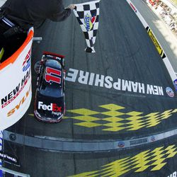 Denny Hamlin crosses the finish line to win the NASCAR Sprint Cup Series auto race at New Hampshire Motor Speedway, Sunday, Sept. 23, 2012, in Loudon, N.H.