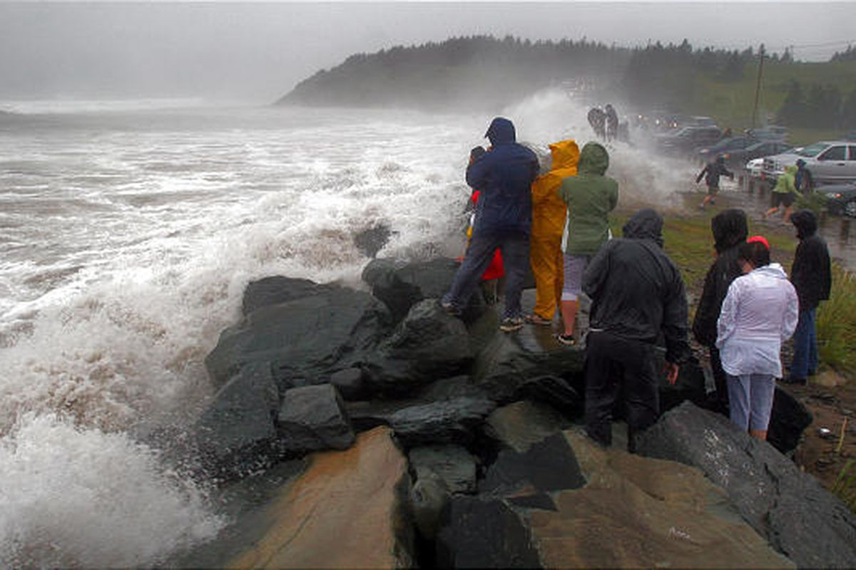 People watch as water breaches a rock wall at Lawrencetown, Nova Scotia,  Sunday.