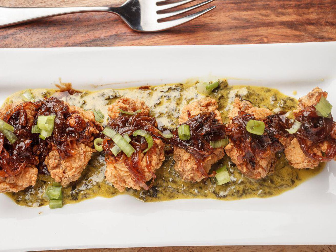 A plate of fried oysters over creamed spinach topped with scallions and caramelized onions