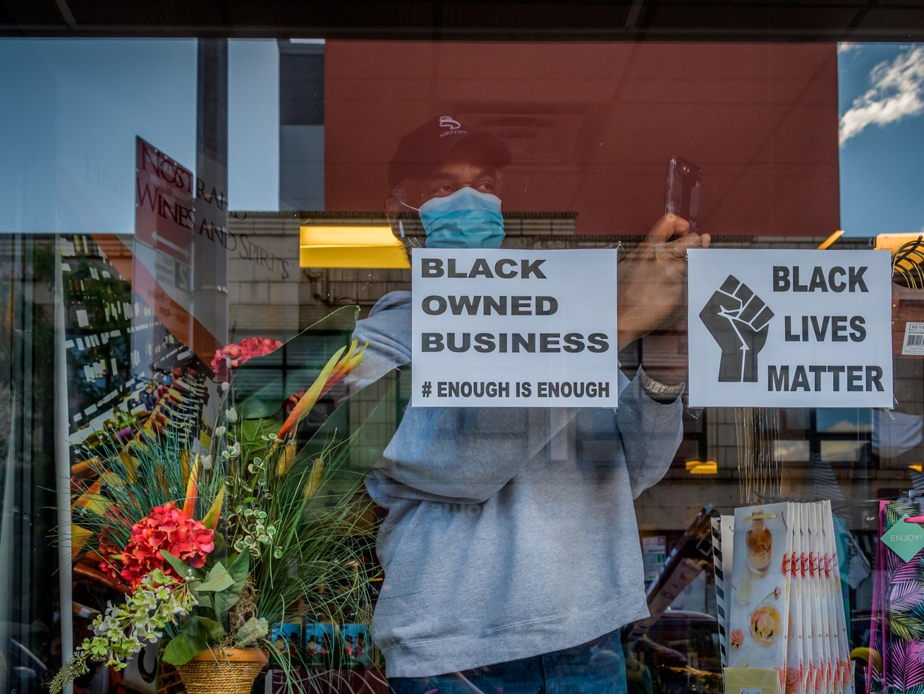 Aman wearing acap andmaskstands insideof ablack owned businessin Crown Heights Brooklyn .