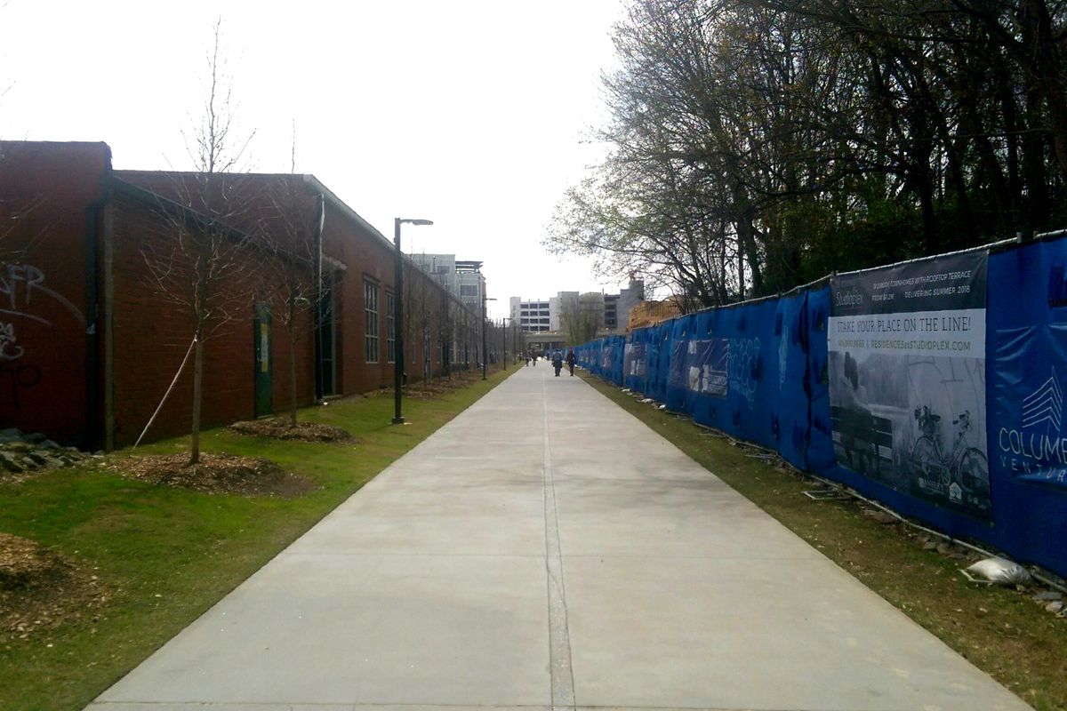 A photo looking down the Eastside Beltline trail, with the Stove Works office complex on the left and construction on the right.