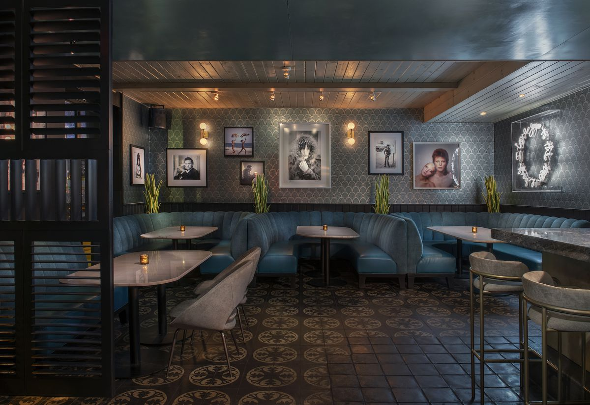 Light blue banquettes and art on the wall at a dim new lounge in Los Angeles.