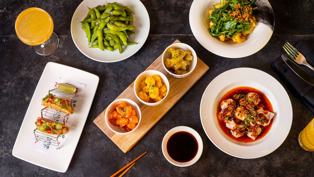 An overhead shot of a table of pan-Asian fare, including dumplings, crispy rice shell tacos, and more.