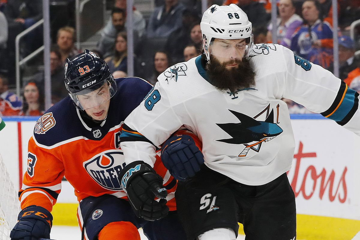 Apr 4, 2019; Edmonton, Alberta, CAN; Edmonton Oilers forward Ryan Nugent-Hopkins (93) and San Jose Sharks defensemen Brent Burns (88) battle for a loose puck during the third period at Rogers Place. Mandatory Credit: Perry Nelson