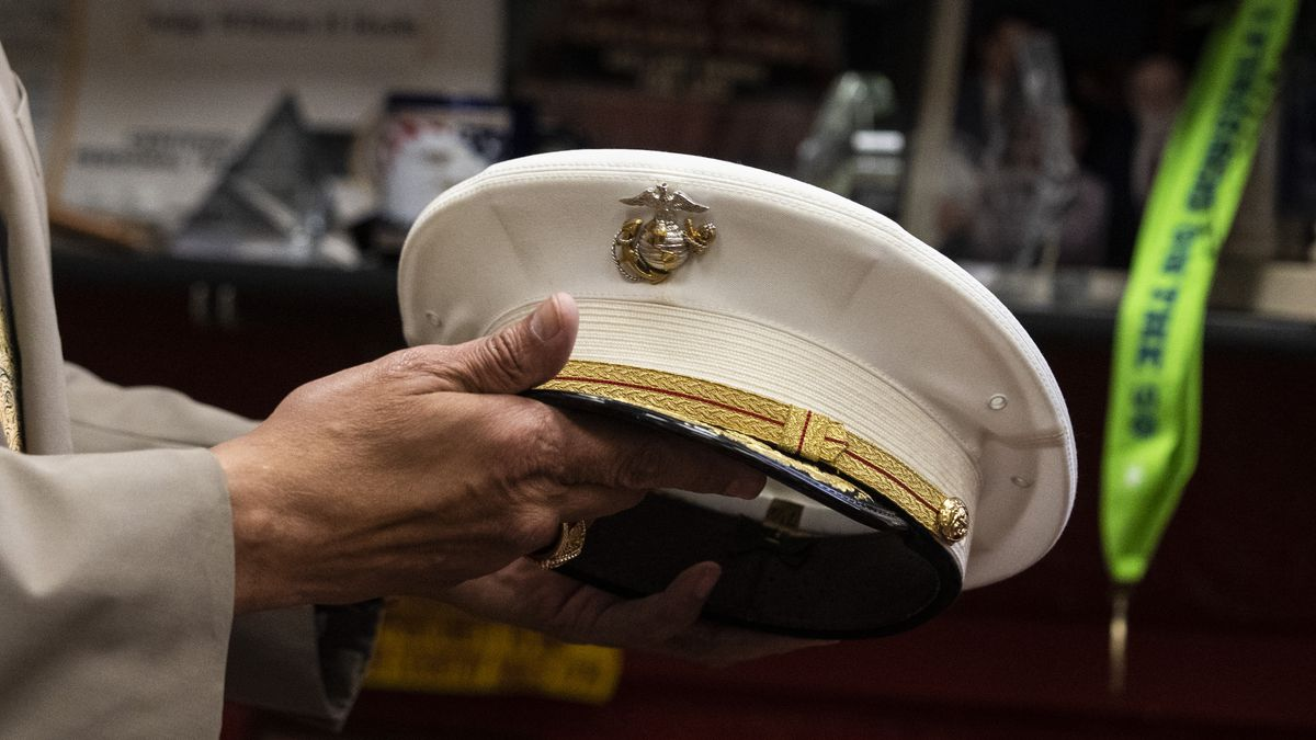 """A Marine corps dress hat, called a """"cover,"""" in the hands of the judge who wore it."""
