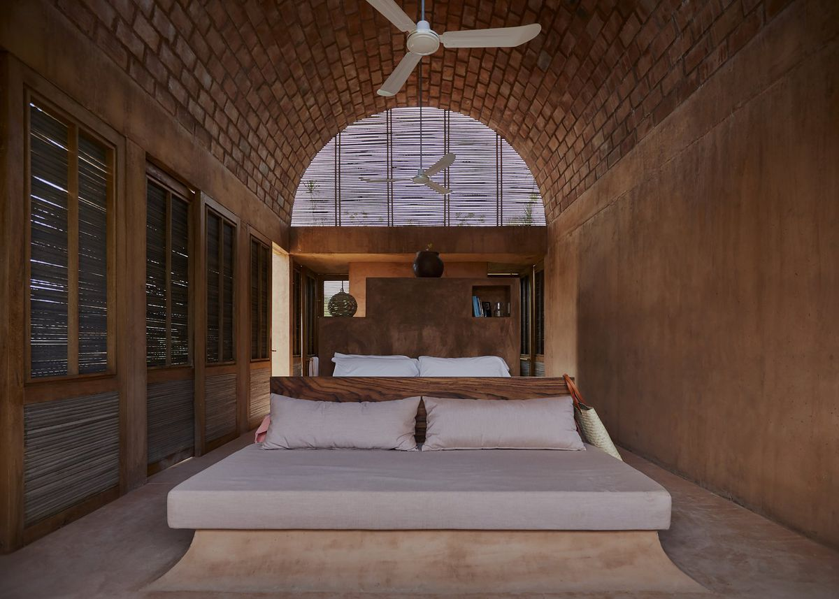 A beige bed sits in a vaulted brick room with reed latticework on the left side and stucco on the right wall.