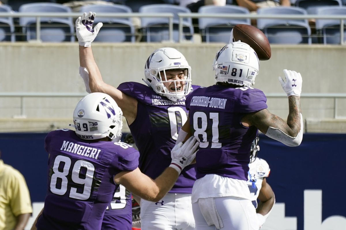 Northwestern tight end John Raine (0) celebrates his touchdown reception against Auburn with teammates Charlie Mangieri (89) and Ramaud Chiaokhiao-Bowman (81) during the first half of the Citrus Bowl.