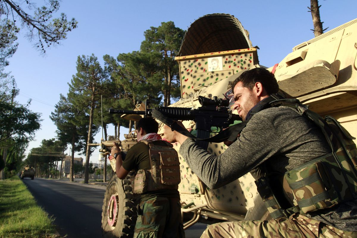 Afghan security personnel take a position during fighting between Taliban and Afghan security forces in Herat province.
