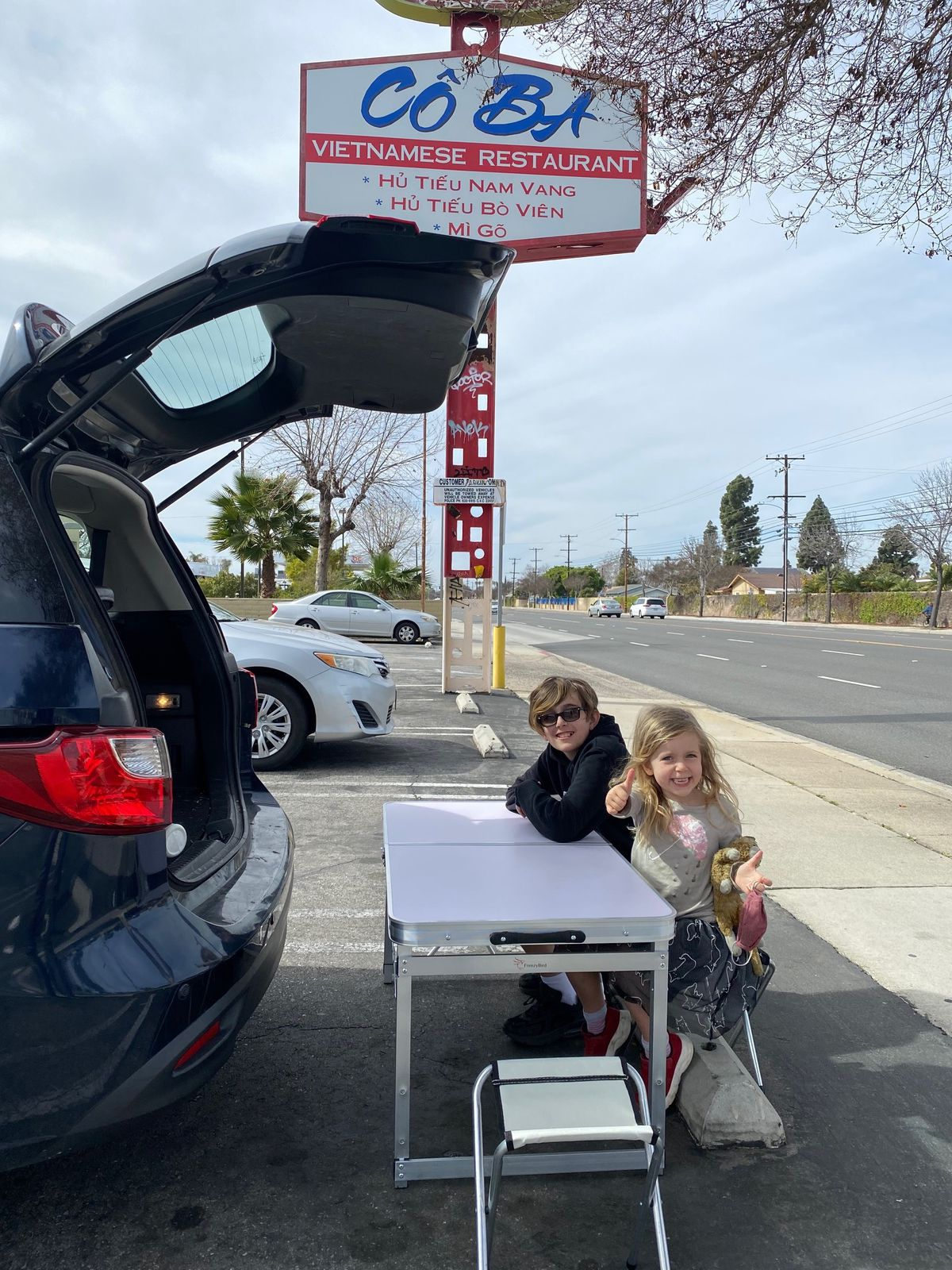 Two children sitting at a folding table set up behind a car with an open trunk