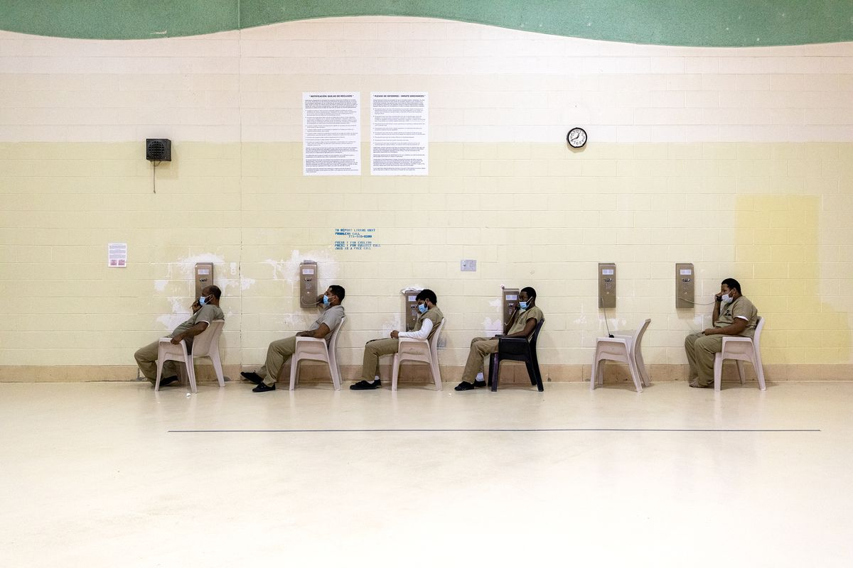 Detainees at the Cook County Jail are seated apart while using the phones.