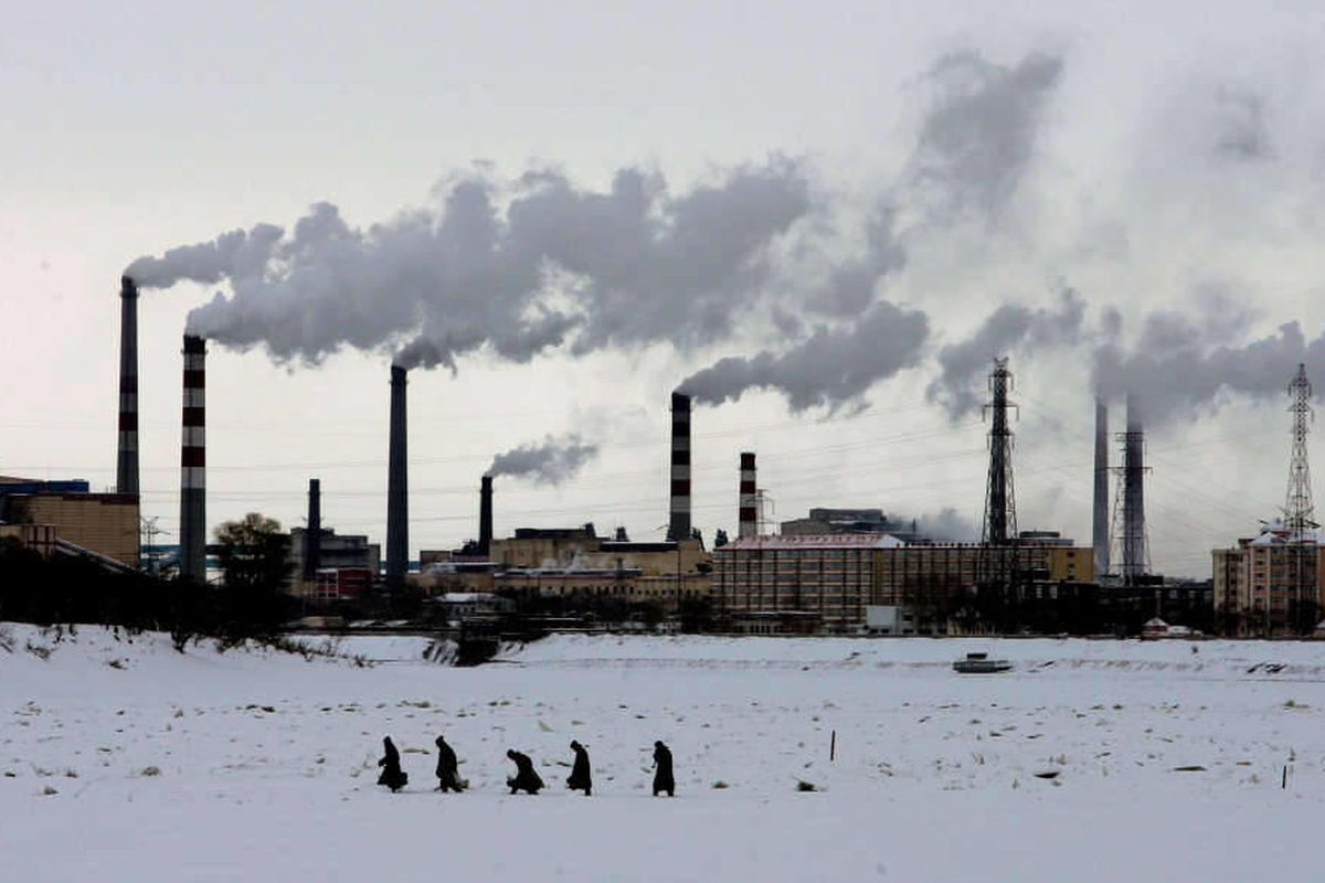 Residents walk across the frozen Songhua River in front of smoke stacks at Jiamusi, in China's northeast Heilongjiang province in this Dec. 4, 2005 file photo. The world's leading climate scientists, in their most powerful language ever used on the issue,