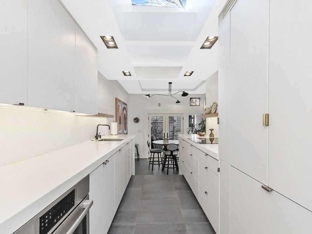 A long, contemporary kitchen with solid cabinetry and countertop space.