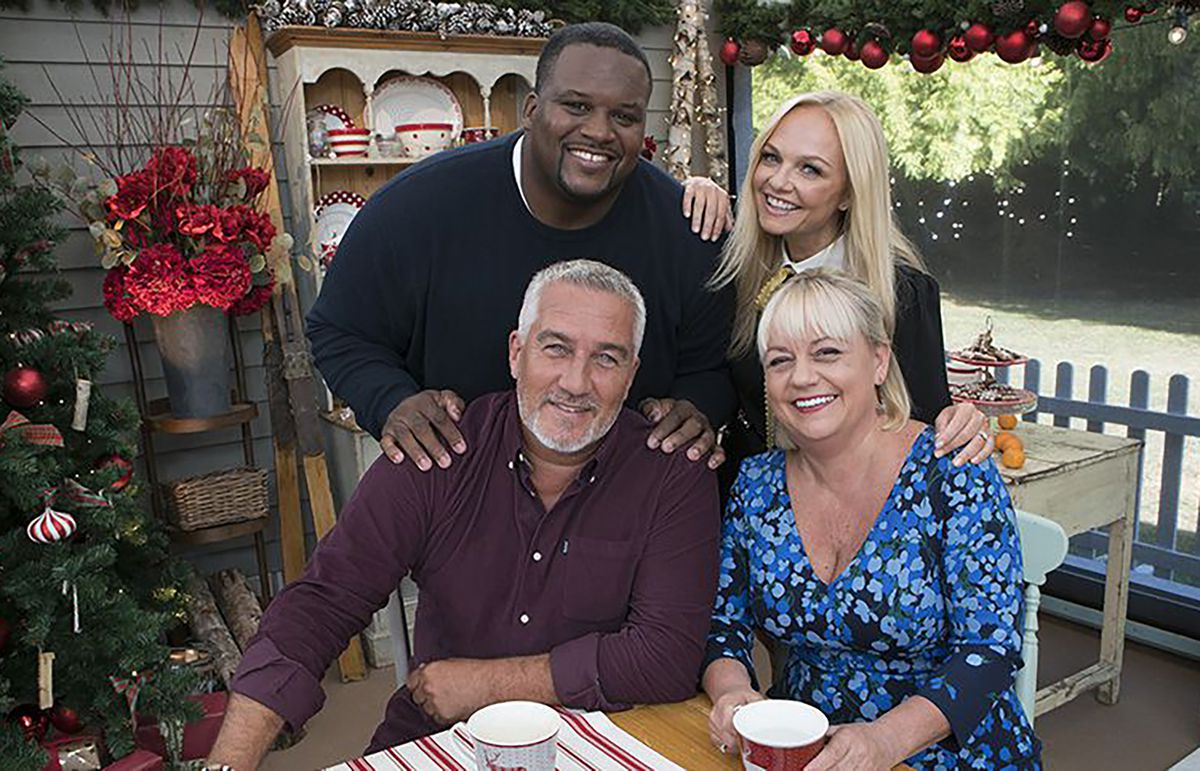 Anthony Adams and Emma Bunton stand behind a seated Paul Hollywood and Sherry Yard with holiday decor in the background.