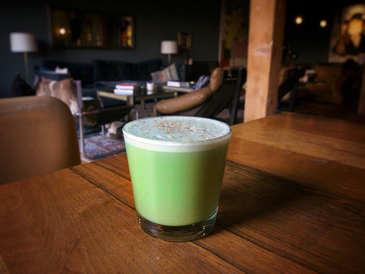 A light green holiday cocktail on a dim wooden table.