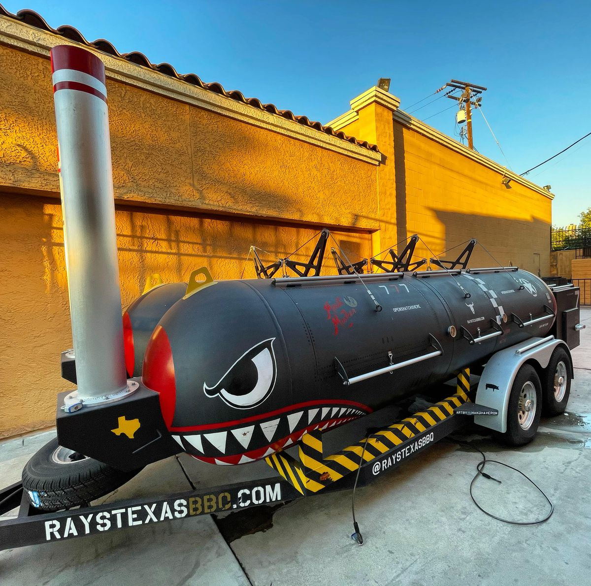 A double barrel smoker painted with angry eyes and sharp teeth in the style of WWII bombers