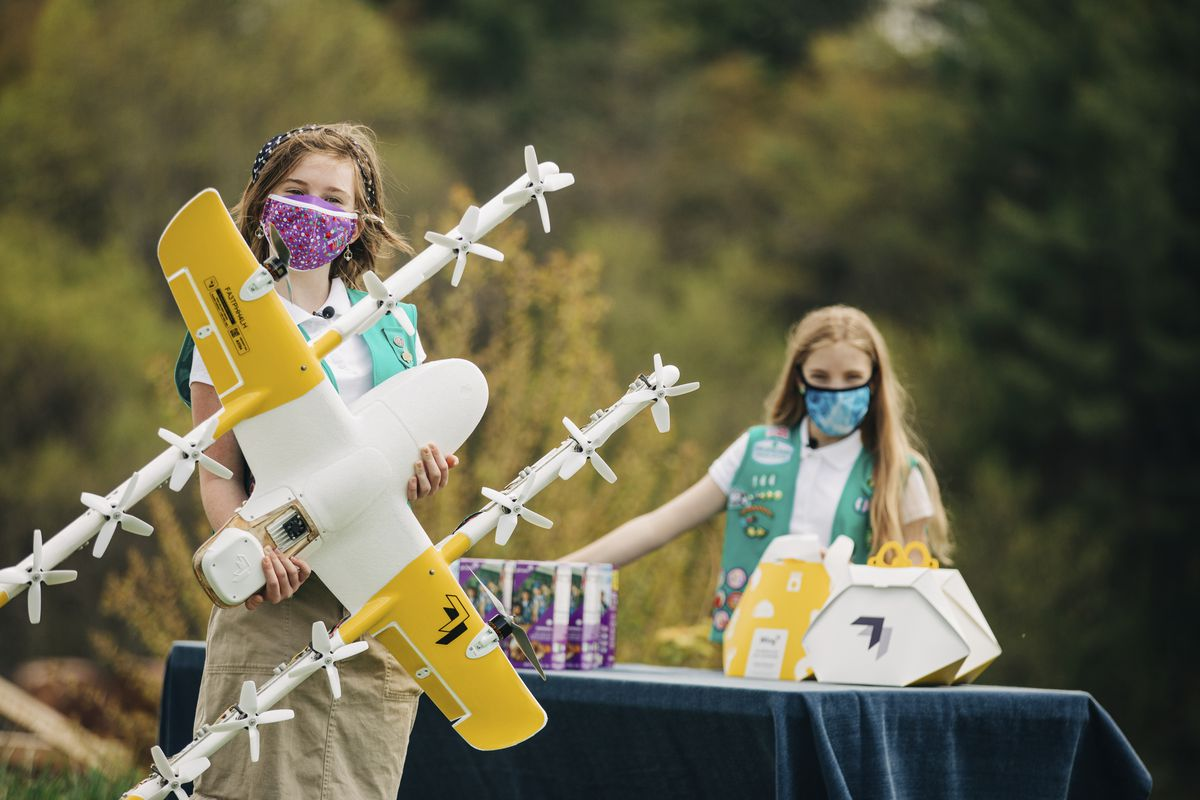 Girl Scouts Gracie Walker (left) and Alice Goerlich with a Wing delivery drone in Christiansburg, Virginia. The company is testing drone delivery of Girl Scout cookies there.