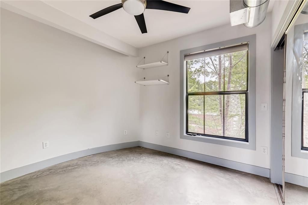 And empty bedroom with large square window, two shelves on the left wall by the window, and a ceiling fan.
