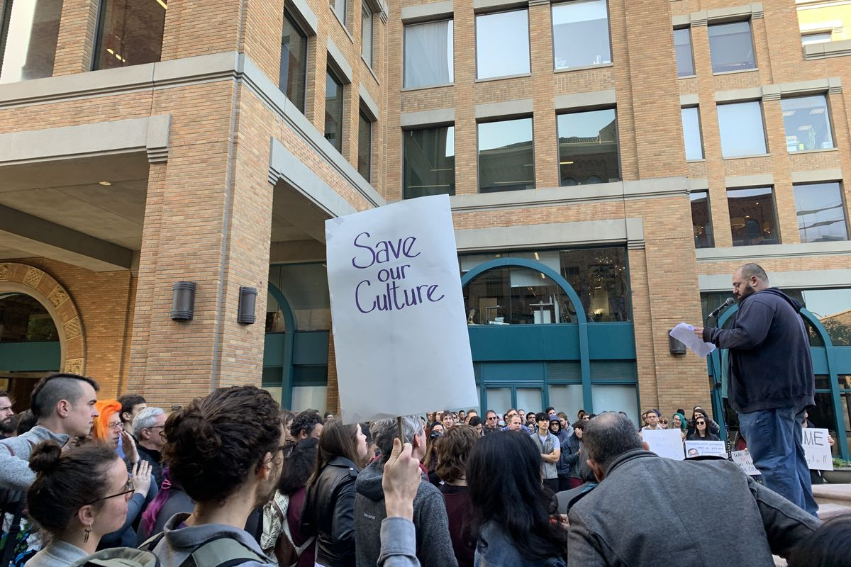 """A man speaks to a large crowd of protesters outside Google's offices in San Francisco; one sign in the crowd says, """"Save Our Culture."""""""